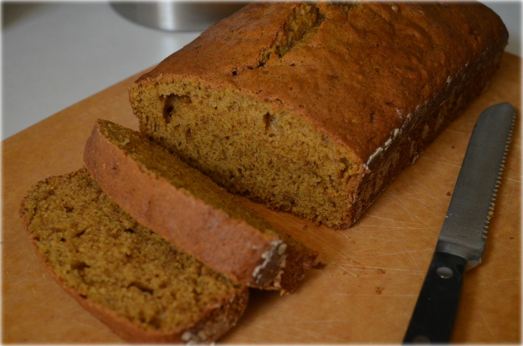 Pumpkin bread loaf being cut in slices