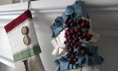 The tops of two shabby chic Christmas stockings hanging on a mantle