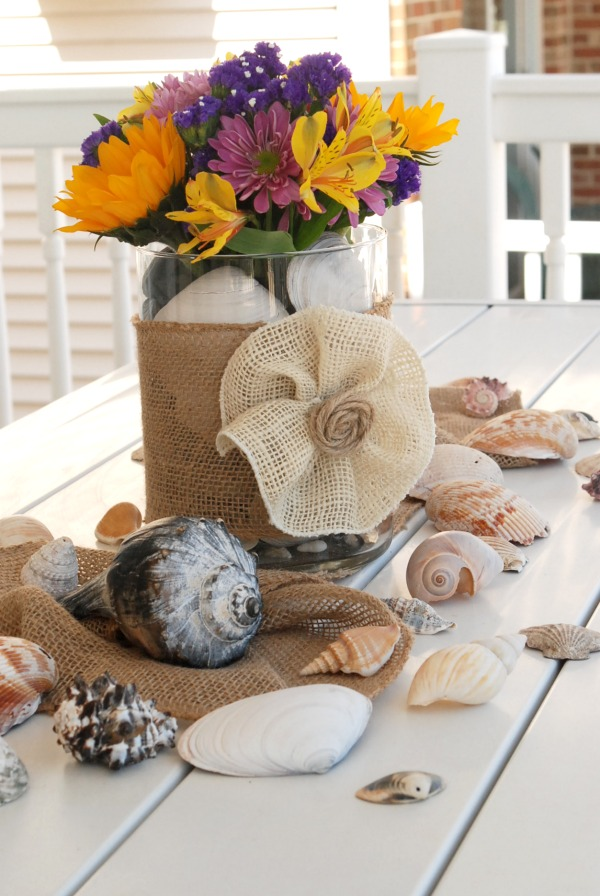 Create a casual, beachy summer centerpiece in just minutes with some flowers, a couple of vases, some burlap ribbon and some seashells.